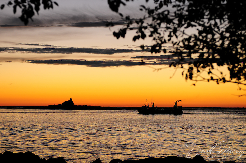 A fishing boat enters Portsmouth Harbor at dawn. Lifeboat station and Whaleback Lighthouse on horizon. Viewed from New Castle, NH