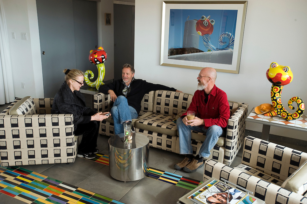 American artists Phillip Maberry & Scott Walker, known as Phillip and Scott, at their new home in Landers, California. .from left to right: Journalist Claudia Steinberg, Scott Walker & Phillip Maberry.For over twenty-five years they have created one-of-a kind ceramic sculptures, hand glazed tiles, reliefs and objects for gallery and museum installations as well as having fulfilled numerous residential and commercial commissions. Their emphasis has always been on modern interpretations of past decorative styles, infused with an optimistic spirit...Text by Claudia Steinberg - full text available from the author:.For the past three decades, American artists Phillip Maberry and Scott Walker have collaborated on quirky, beautiful ceramic objects and tiles. They invested years of their lives building from scratch a stunning three-story house in the Catskills that accommodated giant boulders in its interior.  Once they were done with the time-consuming ceramic decoration of their new home they grew restless. Tired of the long cold winters and humid summers in Highland, NY, they began looking for a place in the sun. After a brief stay in Los Angeles they fell in love with the Mojave desert and decided to build a house with a view of a grand mountain. A New York based architect helped the couple design a stainless steel structure which was shipped to California by train and assembled on site, while the two men lived in a small trailer. It took almost a year to install the house on the ever-shifting sand dune they had inadvertently chosen as their foundation. In the meantime Maberry and Walker have planted their own glow-in-the-dark ceramic mushrooms in their sandy garden, and their charming porcelain creatures based on blow-up beach toys lurk everywhere. Curiously,  their new home has the same modernist, elegant esthetic as their previous house.