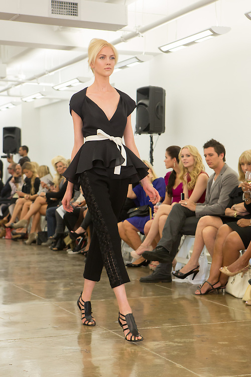 Black capri-length pants with lace insets and black cap-sleeve top with peplum. By Carmen Marc Valvo at the Spring 2013 Fashion Week show in New York.