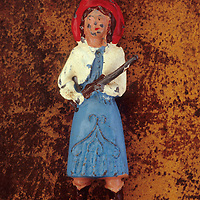 Scratched lead model of American cowgirl wearing embroidered blue dress white jacket red hat brown boots and carrying rifle