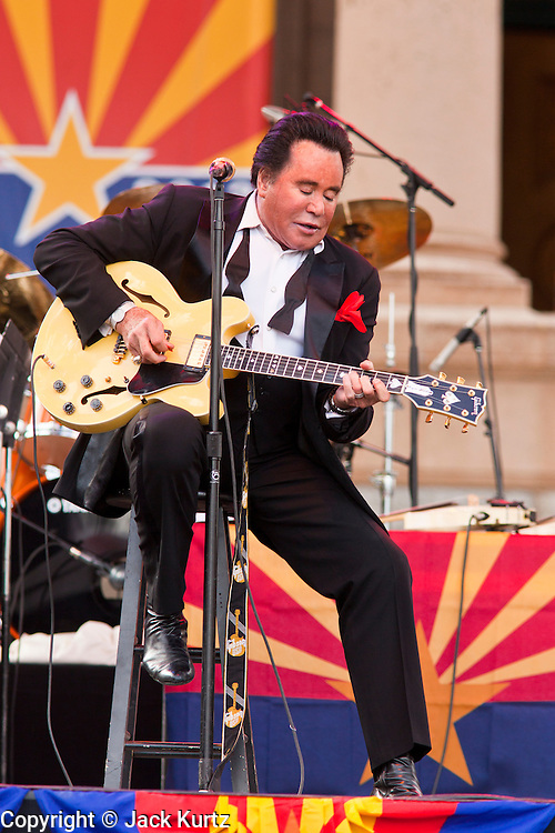 14 FEBRUARY 2012 - PHOENIX, AZ:    WAYNE NEWTON plays guitar during his performance in Phoenix, AZ, Tuesday. Newton, who is originally from Phoenix, performed in front of the state capitol for about an hour Tuesday afternoon at the Arizona centennial. The state of Arizona marked 100 years of statehood with a free party in front of the capitol.   PHOTO BY JACK KURTZ