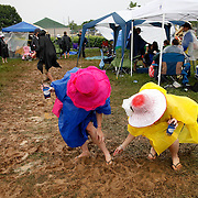 Betty Dean, right, helps her friend Colleen Patrick free her shoe which was stuck in the mud in the infield during the 136th running of the Kentucky Derby at Churchill Downs Saturday May 1, 2010. Photo by David Stephenson