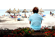 Elder woman sitting relaxed on a wall and watches the beach life. Many retirees hibernate for 6 months in the Canary Islands: British, Russian and German people mostly.