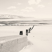 Groynes in shifting white sands at Barmouth Beach North Wales, in brilliant sunshine and at low tide.