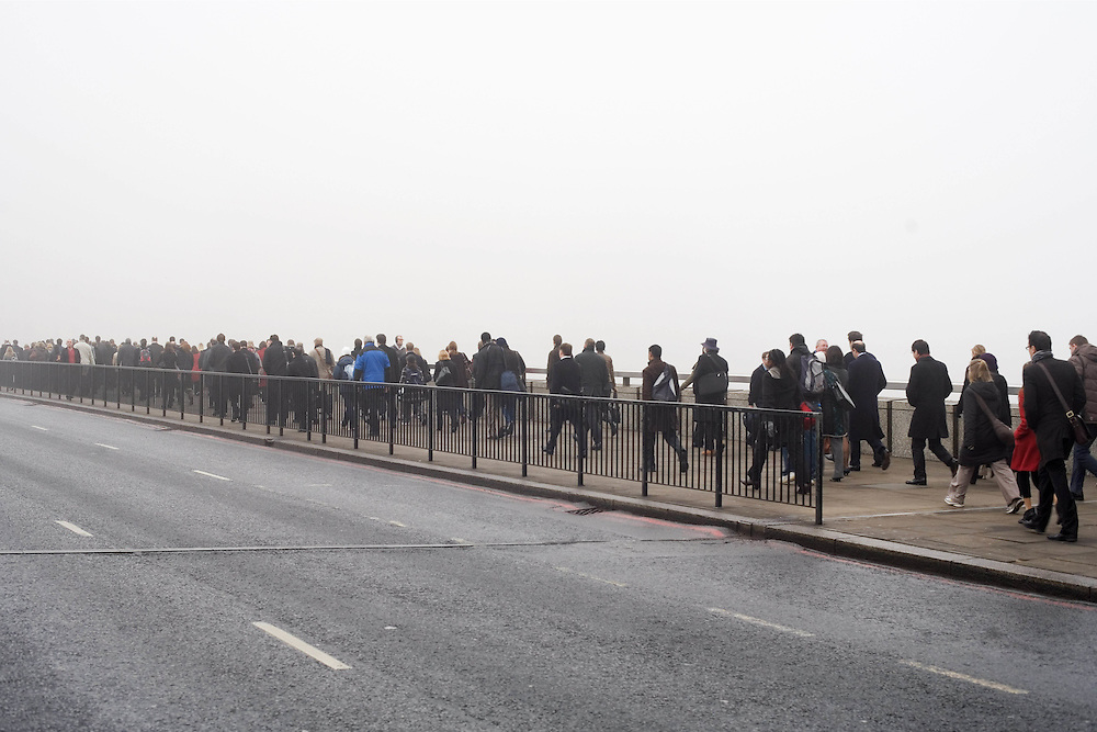 UK. London. Monday morning commuters walk across London bridge in the fog.