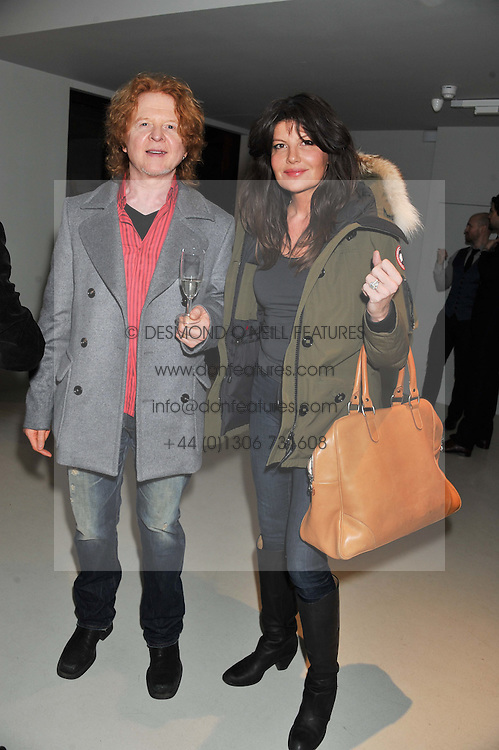 MICK HUCKNALL and his wife GABRIELLA at a private view of Bill Wyman - Reworked held at the Rook & Raven Gallery, 7 Rathbone Place, London W1 on 26th February 2013.