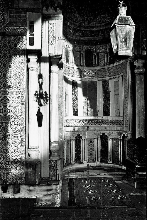 Interior of a typical old Cairo house in Mamluk architectural style.  Sunlight throws a shadow of a lamp in the foreground against the qibla wall beyond.  The chair and water jars indicate that the house is somewhat cared for, if not actually lived in.