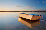 A lone dingy rests in the calm waters of Golden Beach at sunrise.