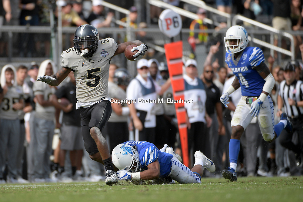 Central Florida wide receiver Dredrick Snelson (5) runs after catching a pass in front of Memphis defensive back Terrell Carter (2), center, and defensive back Josh Perry (4) during the first half of the American Athletic Conference championship NCAA college football game Saturday, Dec. 2, 2017, in Orlando, Fla. (Photo by Phelan M. Ebenhack)
