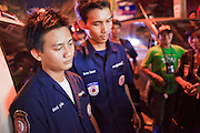 "02 OCTOBER 2009 -- BANGKOK, THAILAND: Members of the Poh Teck Tung Foundation wait to be relieved after they tried in vain to save the life of a man who was in a motorcycle accident in Bangkok. The man died while they were working on him. The 1,000 plus volunteers of the Poh Teck Tung Foundation are really Bangkok's first responders. Famous because they pick up the dead bodies after murders, traffic accidents, suicides and other unplanned, often violent deaths, they really do much more. Their medics respond to medical emergencies, from minor bumps and scrapes to major trauma. Their technicians respond to building collapses and traffic accidents with heavy equipment and the ""Jaws of Life"" and their divers respond to accidents in the rivers and khlongs of Bangkok. The organization was founded by Chinese immigrants in Bangkok in 1909. Their efforts include a hospital, college tuition for the poor and tsunami relief.   PHOTO BY JACK KURTZ"