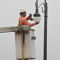 An electricians from C.T. & F., inc. replaces lights and fixtures with L.E.D. versions at the Santa Monica Pier on Thursday, September 13, 2012.