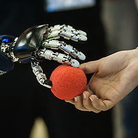 Lyon, France - 19 March 2014: the hand of iCub robot by the Italian Istitute of Technology grabs a ball from a girl's hand at Innorobo 2014, the 4th international trade show on service robotics.