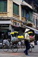 A street vendor wandering past two bicycles with colourful flowers on the back.