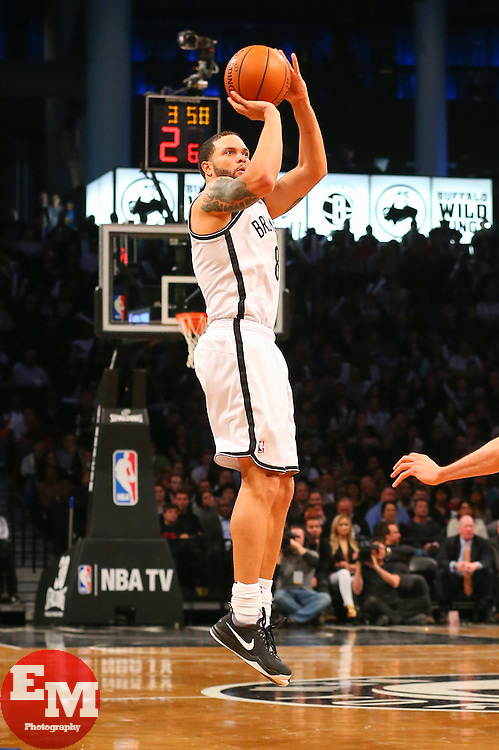 Apr 1, 2014; Brooklyn, NY, USA; Brooklyn Nets guard Deron Williams (8) shoots the ball during the fourth quarter at Barclays Center. The Nets defeated the Rockets 105-96.