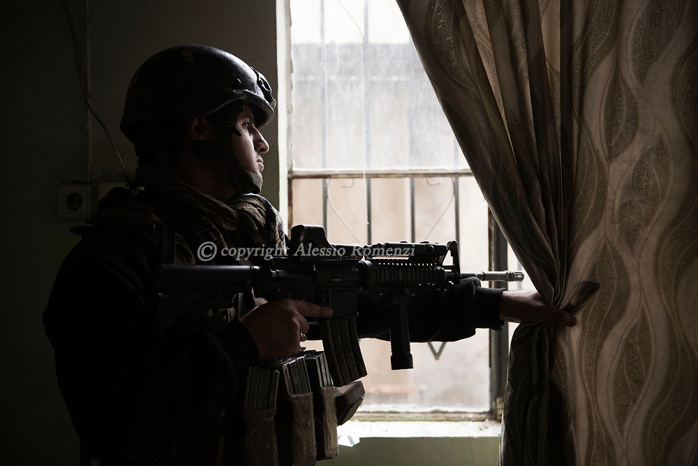 Iraq, Mosul: A Golden Division member stands guard on the window of a newly liberated house in west Mosul. Alessio Romenzi