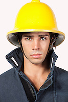 Portrait of young fireman against gray background
