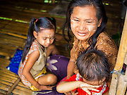 06 JUNE 2014 - IRRAWADDY DELTA,  AYEYARWADY REGION, MYANMAR: A woman with her children in their home in the Irrawaddy Delta (or Ayeyarwady Delta) in Myanmar. The region is Myanmar's largest rice producer, so its infrastructure of road transportation has been greatly developed during the 1990s and 2000s. Two thirds of the total arable land is under rice cultivation with a yield of about 2,000-2,500 kg per hectare. FIshing and aquaculture are also important economically. Because of the number of rivers and canals that crisscross the Delta, steamship service is widely available.   PHOTO BY JACK KURTZ