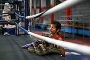 A local thai girl watches more experienced fighters train in the ring at the Rangsit Muay Thai training school. This family owned gym is one of the top schools in Bangkok and has been open for almost 50 years. As well as Thais, every year hundreds of foreign fighters pass through their doors. Some come just to train for fitness, others to enter competitive muay thai events through the schools adjacent boxing stadium where Tuesday night live-to-air fighting events are a weekly occurence..Muay Thai boxing is an ancient fighting form developed in Thailand developed by combining various other forms of SE Asian kickboxing. This brutal sport full of ancient traditions only saw the wearing of modern gloves during training and in boxing matches against foreigners less than 100 years ago where previously only rope-binding of hands was used. Thailand has around 60,000 mauy thai fighters and is the lion's den for anyone wanting to be a success in the sport.