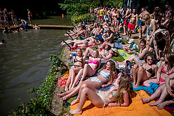 © Licensed to London News Pictures. 07/05/2018. London, UK. People sunbathe near Hampstead Heath Mixed Bathing Pond in north London as temperatures hit 28C on the hottest May bank holiday since 1999 on Monday, May 7, 2018. Photo credit: Tolga Akmen/LNP