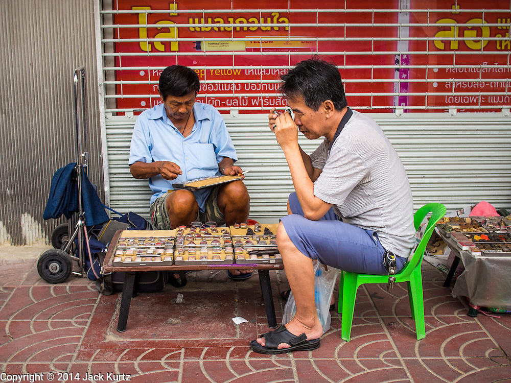 23 AUGUST 2014 - BANGKOK, THAILAND:        A man shops for amulets from a vendor on the sidewalk along Chareon Krung Road in Bangkok. The Thai military junta, formally called the National Council for Peace and Order (NCPO), has ordered street vendors off of the sidewalks in an effort to bring order to Bangkok's chaotic sidewalks. Vendors have complained that the new regulations are hurting them economically but largely complied with the military orders.  PHOTO BY JACK KURTZ
