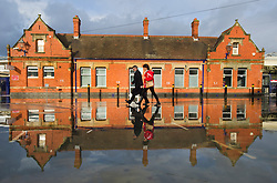Commuters walking past a partly flooded Newbury train station, United Kingdom, Tuesday, 7th January 2014. Picture by i-Images