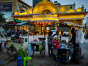 "13 FEBRUARY 2019 - SIHANOUKVILLE, CAMBODIA:  Cambodian street food carts across the street from the Royal Casino, a Chinese casino in Sihanoukville. There are about 80 Chinese casinos and resort hotels open in Sihanoukville and dozens more under construction. The casinos are changing the city, once a sleepy port on Southeast Asia's ""backpacker trail"" into a booming city. The change is coming with a cost though. Many Cambodian residents of Sihanoukville  have lost their homes to make way for the casinos and the jobs are going to Chinese workers, brought in to build casinos and work in the casinos.      PHOTO BY JACK KURTZ"