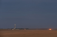 A drill rig and natural gas flares near Ray, North Dakota.