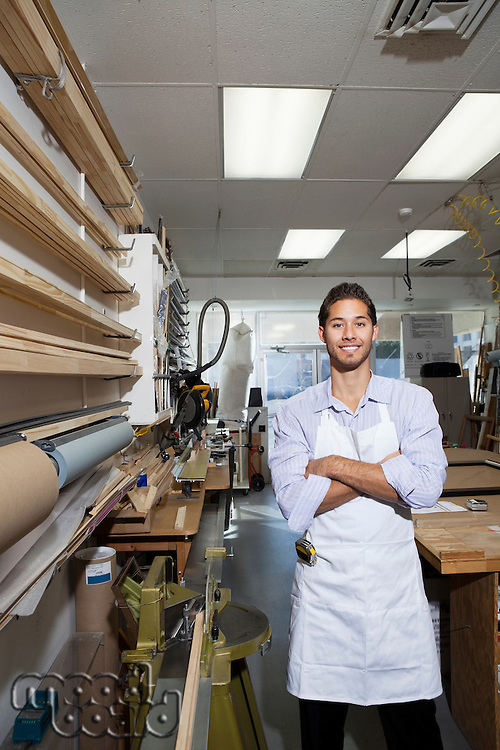 Portrait of a happy skilled worker standing with arms crossed in workshop