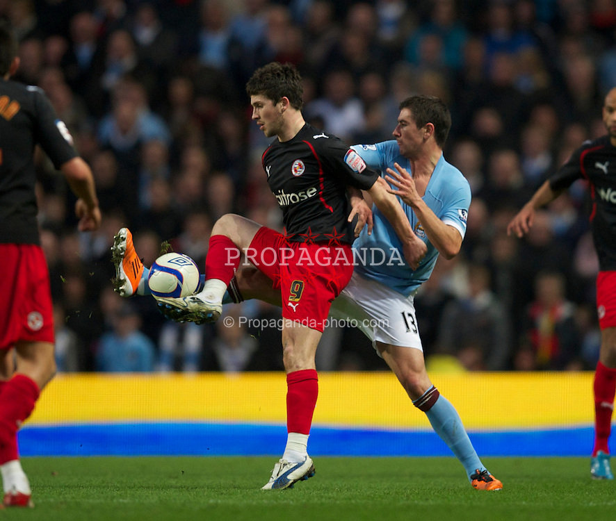 MANCHESTER, ENGLAND - Sunday, March 13, 2011: Manchester City's Aleksandar Kolarov and Reading's Shane Long during the FA Cup 6th Round match at the City of Manchester Stadium. (Photo by David Rawcliffe/Propaganda)