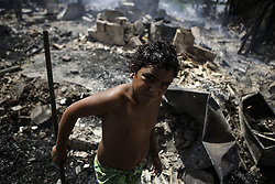 December 12, 2016 - Recife, Brazil - Williams Adriel, just 9 years old, works to help his family, who had all belongings burned. During the morning of Monday (12), the fire hit the favela Vila Santa Luzia, in the city of Recife. Dozens of people had their homes burned by fire and three men had severe burns on their bodies. In Recife, Northeast Brazil, December 12, 2016.December 12, 2016. (Credit Image: © Diego Herculano/NurPhoto via ZUMA Press)