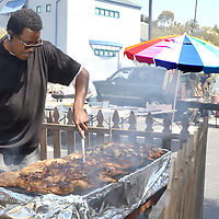 Belizean Dylan Bernard cooks Caribbean jerk chicken during the John Muir School PTA Art and Antique Fair on Saturday, May 5, 2012. The Art and Antique Fair is held on the first Saturday of each month, from 8am to 3pm.