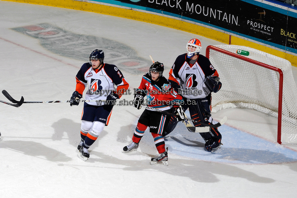 KELOWNA, CANADA, OCTOBER 29: Cody Chikie #14 of the Kelowna Rockets looks for the pass in front of Kamloops goaltender Cam Lanigan #30  while being checked by Tyler Hansen #2 of the Blazers as the Kamloops Blazers visit the Kelowna Rockets  on October 29, 2011 at Prospera Place in Kelowna, British Columbia, Canada (Photo by Marissa Baecker/Shoot the Breeze) *** Local Caption *** Cody Chikie; Cam Lanigan;Tyler Hansen;