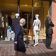 Elderly woman walks past naked mannequin on sidewalk, Pisa, Tuscany, Italy