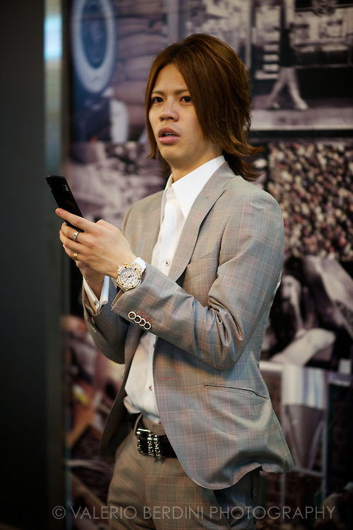 A host in his smart suit and mobile waits for his encounter in D?tonbori. Osaka, Japan 2013