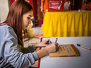 10 JANUARY 2014 - BANGKOK, THAILAND: A woman writes a prayer on a roof tile at Wat Mangkon Kamalawat in the Chinatown section of Bangkok. It is the largest Mahayana (Chinese style) Buddhist temple in Chinatown.       PHOTO BY JACK KURTZ