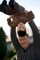 United States, Washington, Bellevue, father holding son (age 3) up in the air.  MR