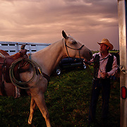 Mike Moyle unloads his horse before sunrise as he and a dozen other cowboys helped in a bi-annual cattle roundup at the Bar B ranch near Albia, Iowa.  Calves were roped and seperated from the herd for vaccinations, branding and the placement of growth stimulant implants.  The male calves were also castrated.  Owner Catherine Bay runs the operation with a herd of over 2,000 cattle.