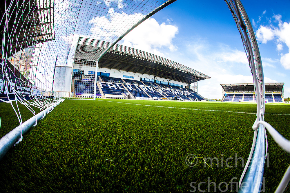 The new plastic pitch and the Main stand seen through the goal net, at The Falkirk Stadium, or the Scottish Championship game v Hamilton. The woven GreenFields MX synthetic turf and the surface has been specifically designed for football with 50mm tufts compared with the longer 65mm which has been used for mixed football and rugby uses.  It is fully FFA two star compliant and conforms to rules laid out by the SPL and SFL.<br />