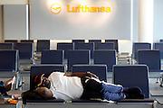 Frankfurt am Main | April 19 2010<br /> Durch eine riesige Aschewolke, die durch einen Ausbruch von Vulkan Eyjafjallajoekull auf Island ausgestossen wurde, kommt der Flugverkehr ueber fast ganz Europa zum Erliegen, etwa 800 Fluggaeste sind im Transit in Terminal 1 gestrandet, sie haben kein Visum und koennen nicht nach Deutschland einreisen. Hier: Ein gestrandeter Passagier schlaeft auf einer Sitzbank im Wartebereich in Terminal 1 unter einem Lufthansa-Logo. @peter-juelich.com [No Model Release | No Property Release]