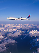 Boeing 777 in flight over mountain tops.