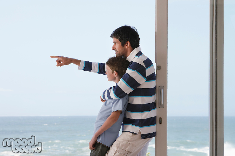Father pointing  out to sea standing in doorway with son