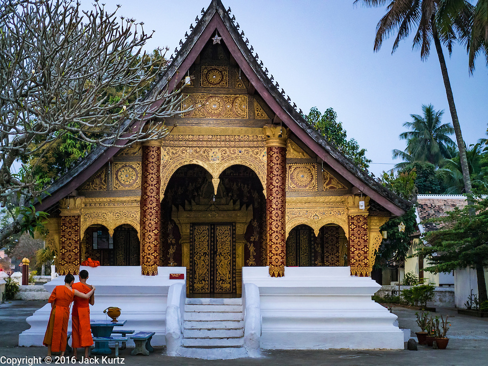 "11 MARCH 2016 - LUANG PRABANG, LAOS:  Buddhist monks wait to start the morning tak bat in Luang Prabang. Luang Prabang was named a UNESCO World Heritage Site in 1995. The move saved the city's colonial architecture but the explosion of mass tourism has taken a toll on the city's soul. According to one recent study, a small plot of land that sold for $8,000 three years ago now goes for $120,000. Many longtime residents are selling their homes and moving to small developments around the city. The old homes are then converted to guesthouses, restaurants and spas. The city is famous for the morning ""tak bat,"" or monks' morning alms rounds. Every morning hundreds of Buddhist monks come out before dawn and walk in a silent procession through the city accepting alms from residents. Now, most of the people presenting alms to the monks are tourists, since so many Lao people have moved outside of the city center. About 50,000 people are thought to live in the Luang Prabang area, the city received more than 530,000 tourists in 2014.      PHOTO BY JACK KURTZ"