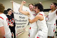 Post Falls High's Jared Kennedy, Marcus Colbert and Shawn Reid celebrate in the locker room with their team following the Trojan's first championship win since 1964 at the state 5A boys basketball championship game Saturday at the Idaho Center in Nampa.