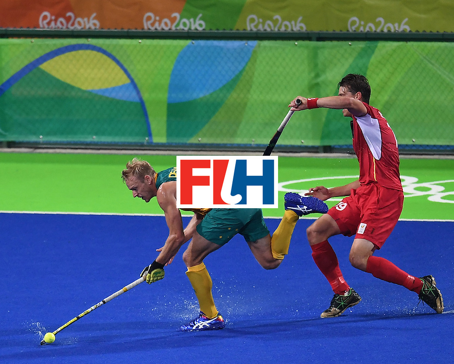 Australia's Tim Deavin (L) vies for the ball with Belgium's Felix Denayer during the men's field hockey Belgium vs Australia match of the Rio 2016 Olympics Games at the Olympic Hockey Centre in Rio de Janeiro on August, 9 2016. / AFP / MANAN VATSYAYANA        (Photo credit should read MANAN VATSYAYANA/AFP/Getty Images)