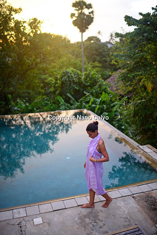 Young attractive woman enters an infinity edge swimming pool at The Dutch House, Galle, Sri Lanka
