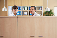 Two office workers smiling behind cubicle