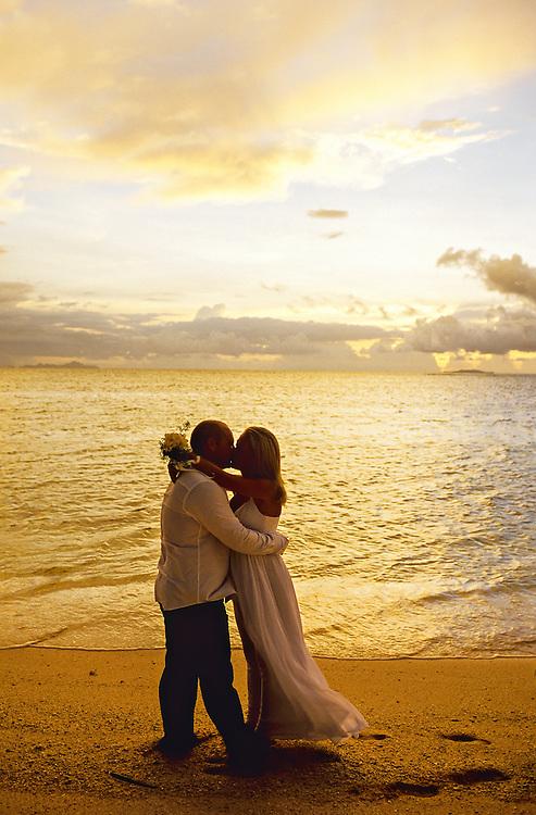 Newlywed couple kissing after their beach wedding ceremony, Vomo Island Resort, Fiji Islands