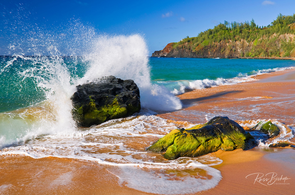 Crashing surf at Secret Beach (Kauapea Beach), Kilauea Lighthouse visible, Kauai, Hawaii USA
