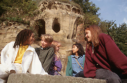 Multiracial group of teenagers sitting outside caves talking,