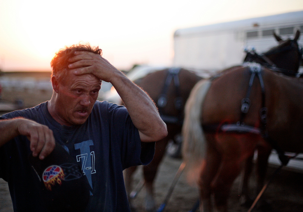 "Charlie Beeman takes a break after several pulls with his two teams of horses during a horse pulling competition at the Mercer County Fair in Aledo, IL on Thursday, July 14.  Beeman is involved in horse pulling 7 days a week, as he makes his living as a logger and sledges trees with his horses.  ""7 days a week, I ain't got no time for myself,"" says Charlie."